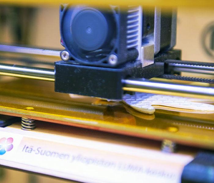 3D-tulostin tulostaa valkoista kappaletta.