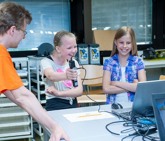 Lapsi kokeilee hymyillen puristusvoimakapulaa ja katsoo yhdessä toisen lapsen ja aikuisen kanssa tulosta kannettavalta tietokoneelta.