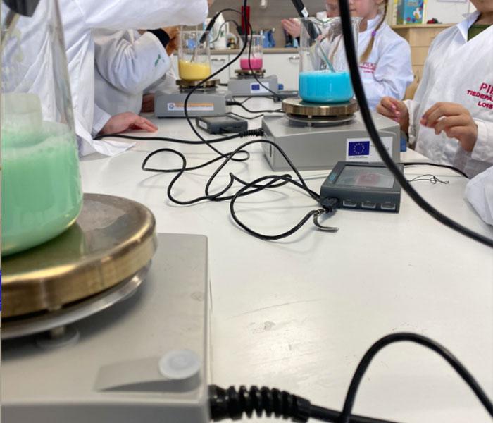 Neljä laitteistoa pöydällä, joita tutkii lapset tutkijantakeissaan. Laitteistot ovat kuumennuslevyt, joiden päällä on dekantterilasit täynnä eriväristä nestettä sekä niissä digitaaliset lämpömittarit.