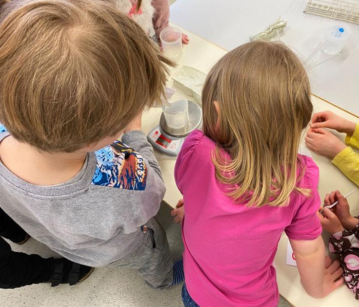 Kaksi lasta kaatavat nestettä vaa'alla olevaan dekantterilasiin.