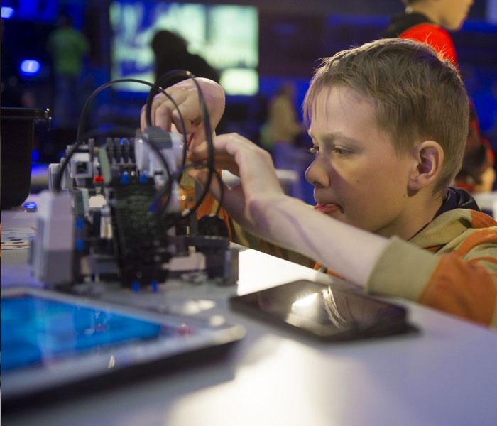 Lapsi tutkii tai muokkaa legorobottia.