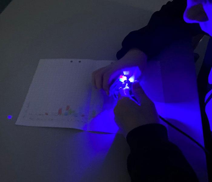Lapsi pitää käsissään ledivaloa. Taustalla on paperi, jossa on koodisto eri lediväreille.