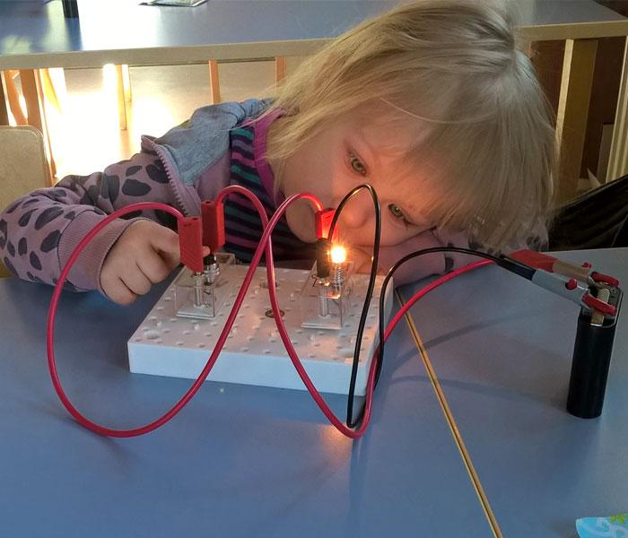 Lapsi katsoo palavaa lamppua, joka on kytketty punaisilla johdoilla virtapiirilevyyn ja paristoon.