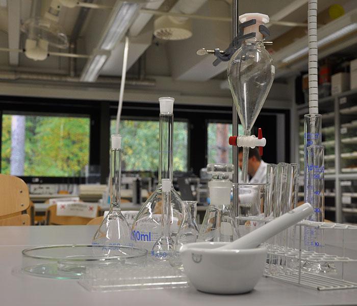 Kemian lasivälineistöä koottuna pöydälle.