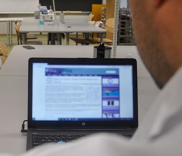 Kuvituskuva, jossa henkilö katsoo kannettavan tietokoneen ruutua.