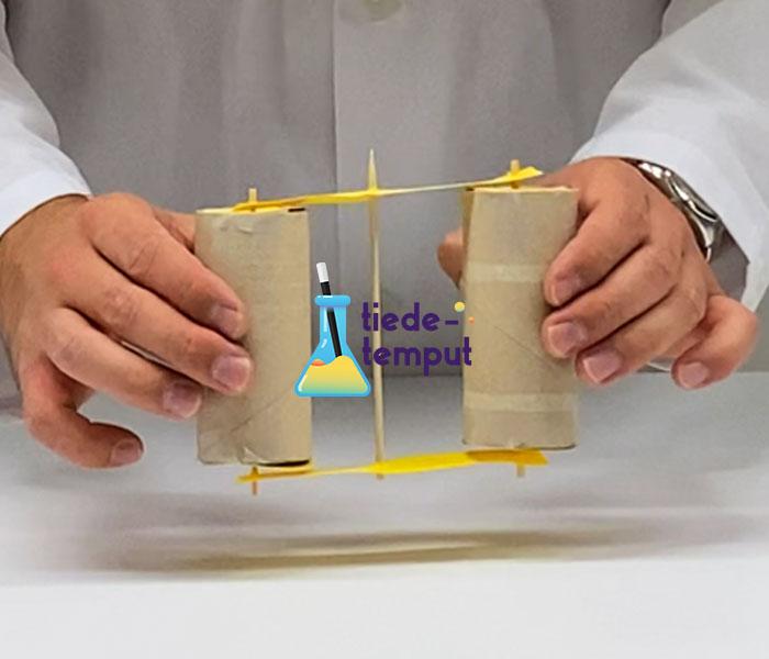 Kuvassa mäkiauto, joka on tehty kahdesta WC-paperihylsystä ja ne on yhdistetty grillitikuilla. Mäkiautoa pidetään käsissä. Kuvan keskellä Tiedetemput-logo