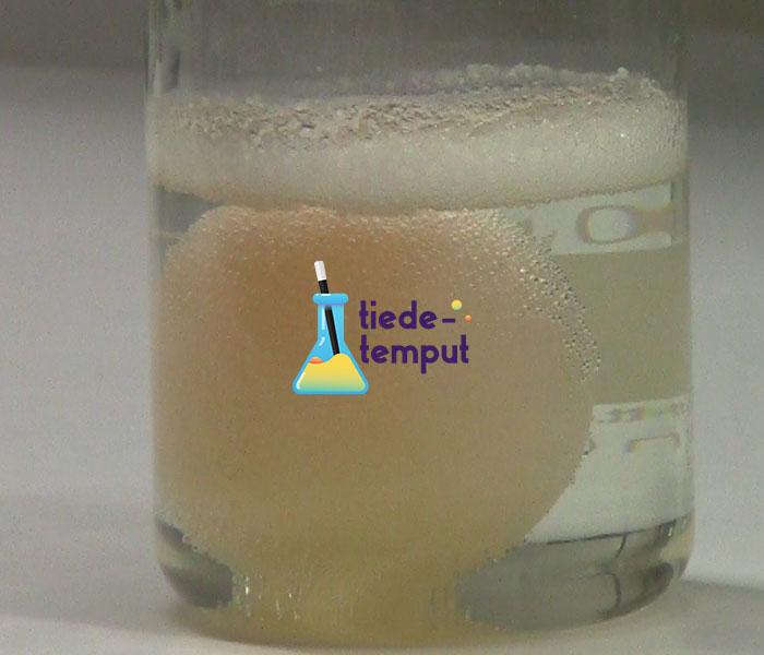 Dekantterilasissa on kirkasta nestettä ja kananmuna, joka on kellertävä. Kuvassa lisäksi tiedetemput logo.