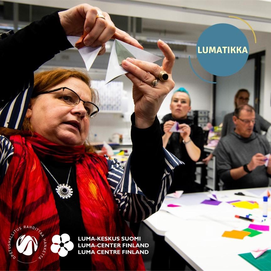 Hnekilö pitää paperista kolmiota ja esittelee sitä takanaan oleville henkilöille. Kuvassa on myös LUMA-keskus Suomen, Opetushallituksen ja LUMATIKAn logot.